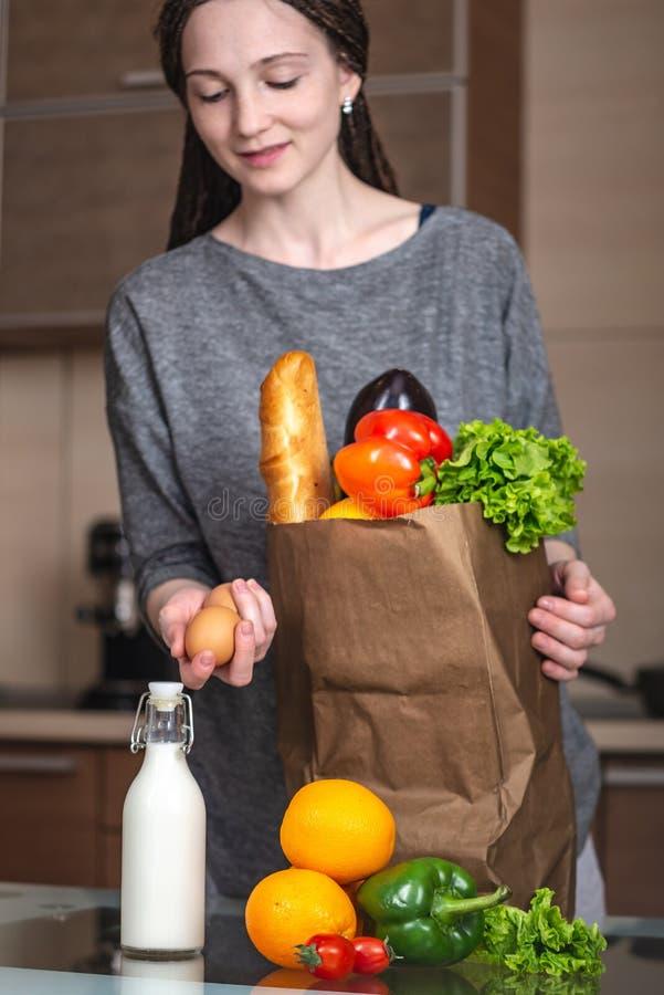 Bolsa de papel llena de la tenencia de la mujer joven con los productos en manos en el fondo de la cocina Alimento biol foto de archivo libre de regalías