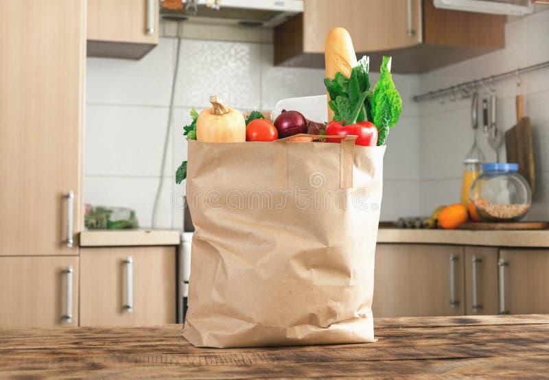 Bolsa de papel por completo de la comida sana en una tabla de madera fotografía de archivo libre de regalías