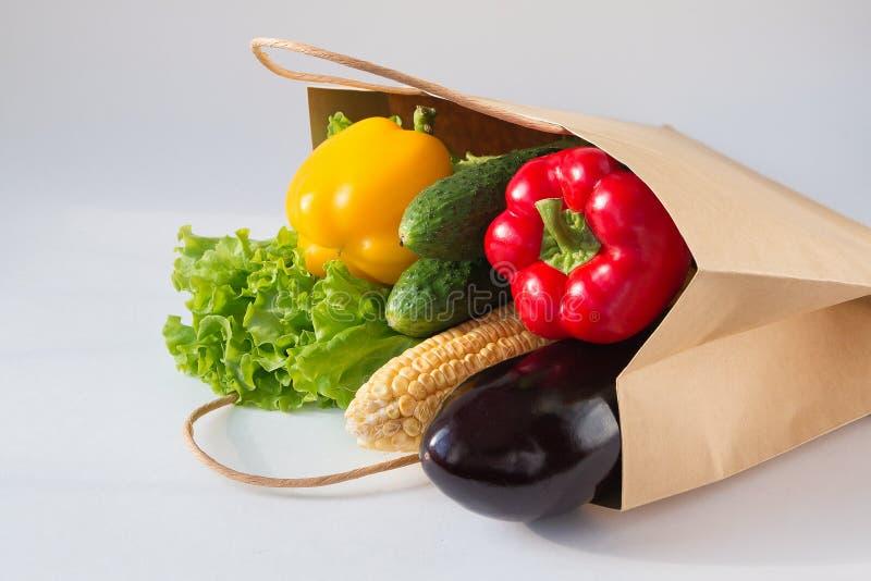 Bolsa de papel por completo de verduras frescas en fondo ligero Pimienta dulce, pepinos, maíz, ensalada, berenjena Vista lateral fotos de archivo