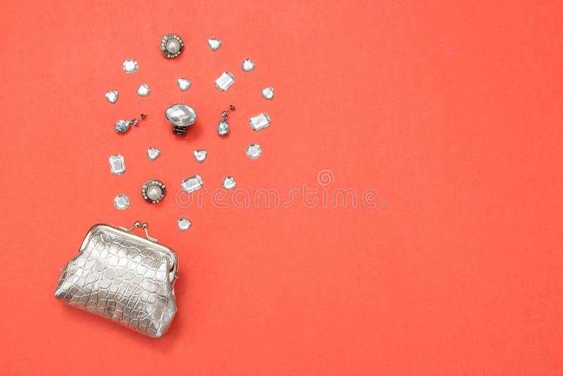 Bolsa, gemas e joia de prata no fundo cor-de-rosa imagem de stock