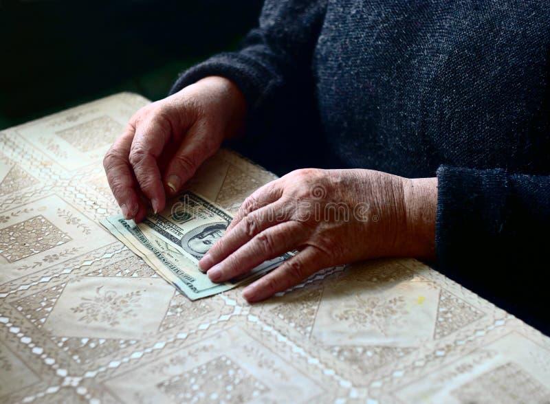 Bolsa magra As mãos e as notas de dólar da mulher adulta na tabela, tiro do contraste, foco seletivo, DOF muito raso foto de stock royalty free