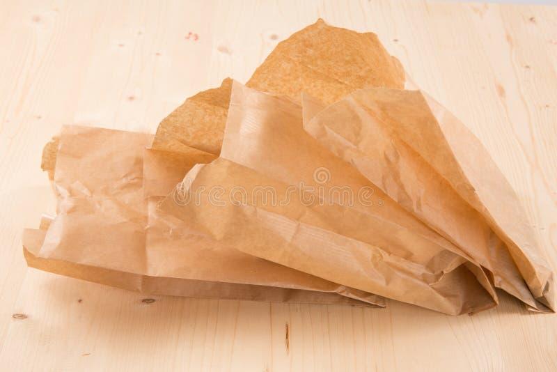 Bolsa reciclada de empaquetado del papel de Kraft en fondo de madera con la trayectoria de recortes fotos de archivo