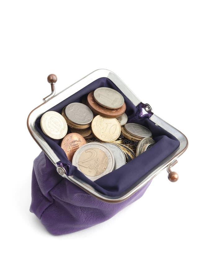 A bolsa violeta está cheia das moedas fotos de stock royalty free