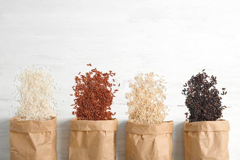 Bolsas de papel con diversos tipos de arroz en el fondo de madera blanco, visión superior fotos de archivo
