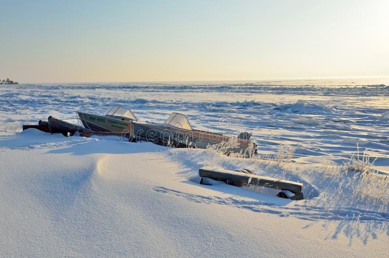Bolshoy Kadilniy, Baikal See, Russland, März, 06, 2017 Boote auf dem Ufer vom Baikalsee nahe Kap Bolshoy Kadilniy lizenzfreies stockfoto