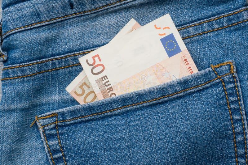 Bolsillo de los vaqueros con cincuenta billetes de banco del euro cerca para arriba fotografía de archivo