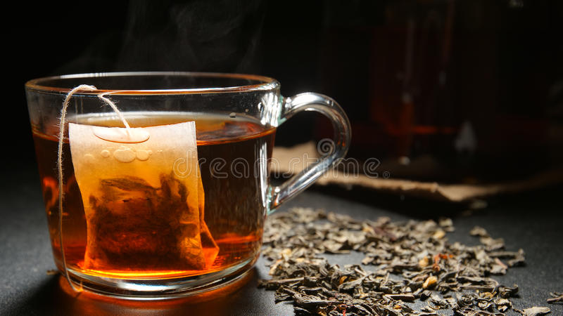 Bolsita de té en una taza de té caliente en una tabla imagen de archivo libre de regalías