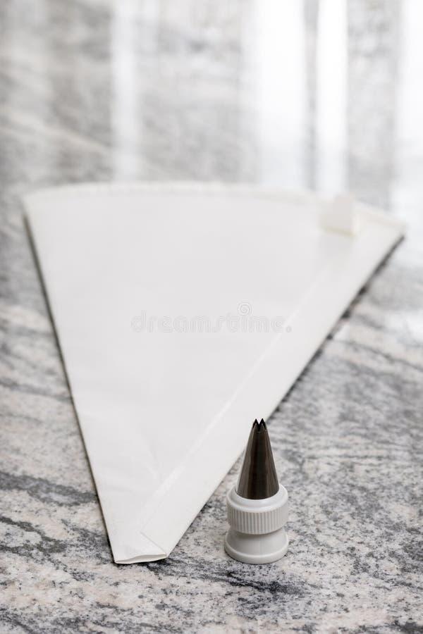 Bolso aflautado de los pasteles blancos en la tabla gris del fondo del granito fotos de archivo libres de regalías
