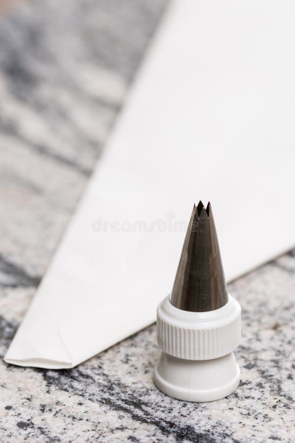 Bolso aflautado de los pasteles blancos en la tabla gris del fondo del granito foto de archivo libre de regalías