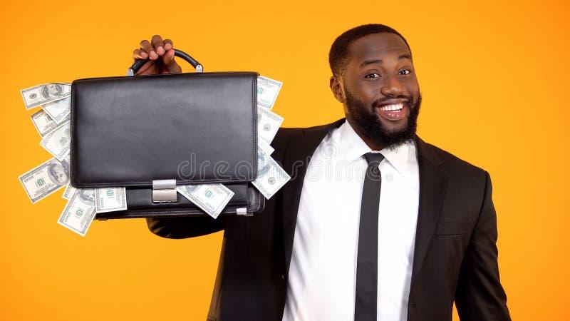 Bolso afroamericano hermoso divertido de la demostraci?n del hombre de negocios con el efectivo del d?lar, dinero imagen de archivo