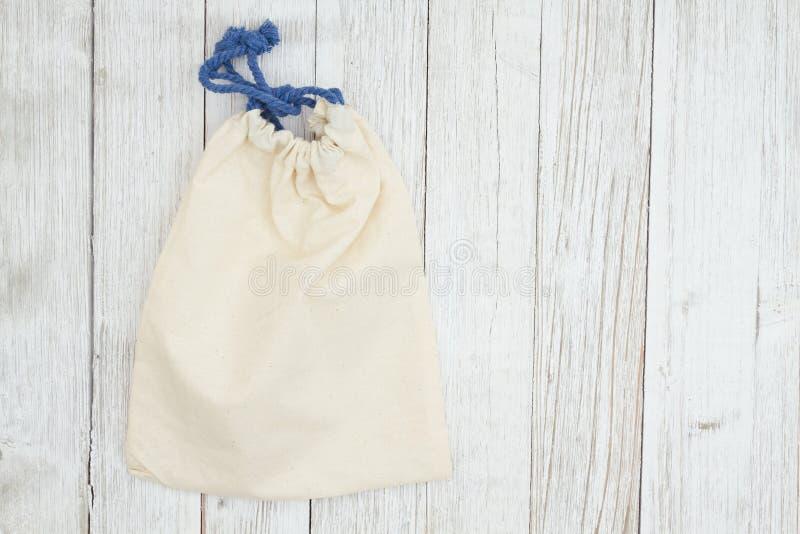 Bolso beige de la lona en fondo texturizado lechada de cal resistido de madera foto de archivo libre de regalías