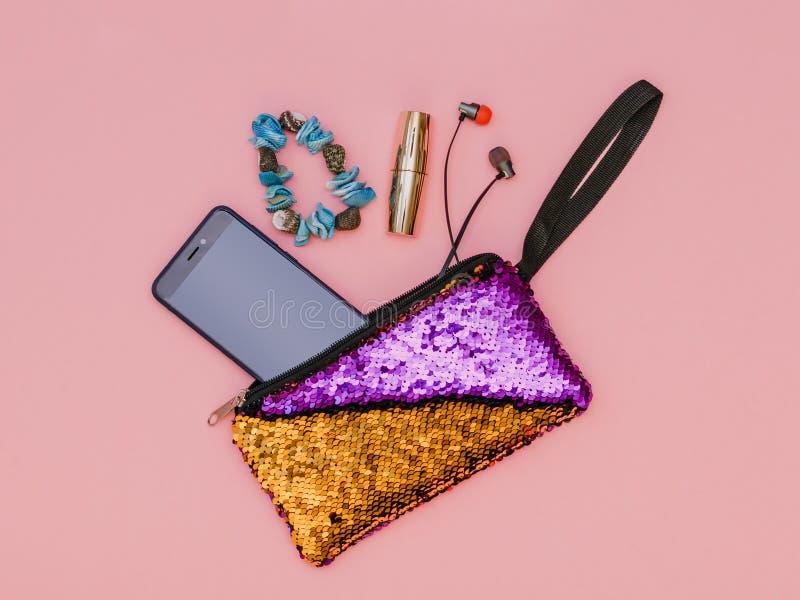 Bolso bicolor con los auriculares, el teléfono, la pulsera y el lápiz labial en fondo rosado Color en colores pastel Endecha plan fotografía de archivo libre de regalías
