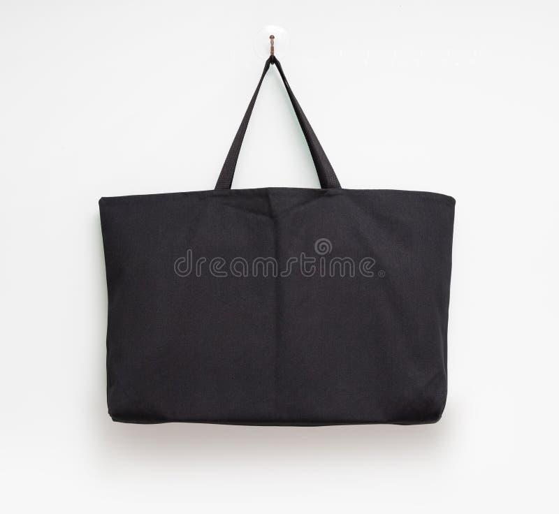 Bolso colgante de la tela en el fondo blanco de la pared Materia textil de la bolsa que hace compras para el montaje o su plantil fotos de archivo
