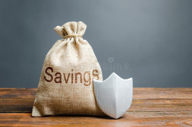 Bolso con el escudo de los ahorros y de la protecci?n de las palabras Concepto de protecci?n y protecci?n de los ahorros y del ef foto de archivo