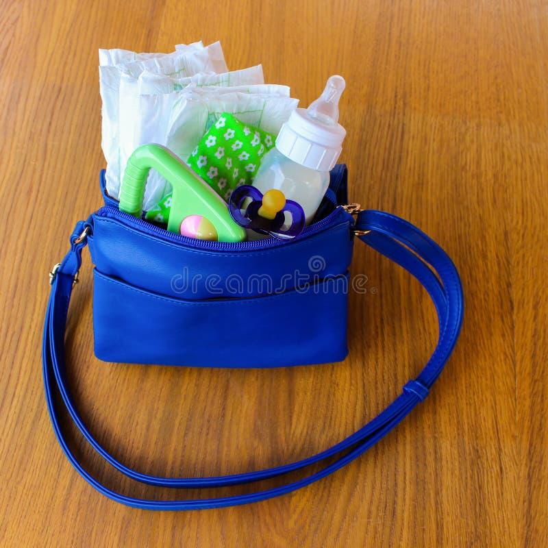 bolso con los artículos al cuidado para el niño fotos de archivo