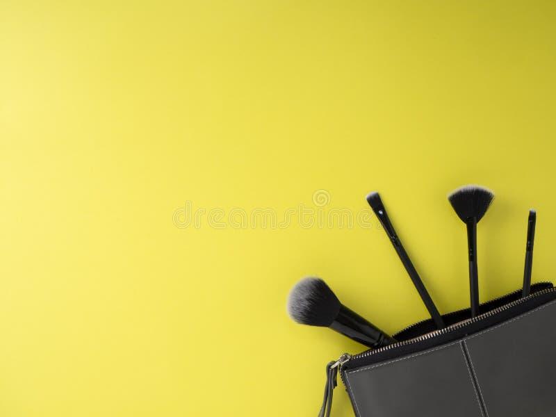 Bolso con los cepillos del maquillaje, cosméticos, fondo amarillo foto de archivo libre de regalías