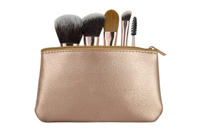 Bolso cosmético de lujo del viaje con el equipo esencial de los cepillos para el maquillaje, productos de belleza aislados en el  foto de archivo