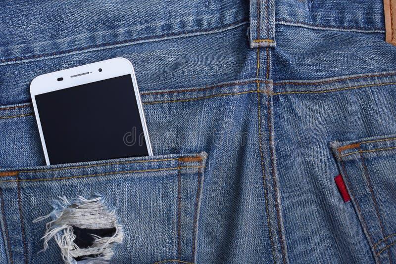Bolso das calças de brim com smartphone imagem de stock