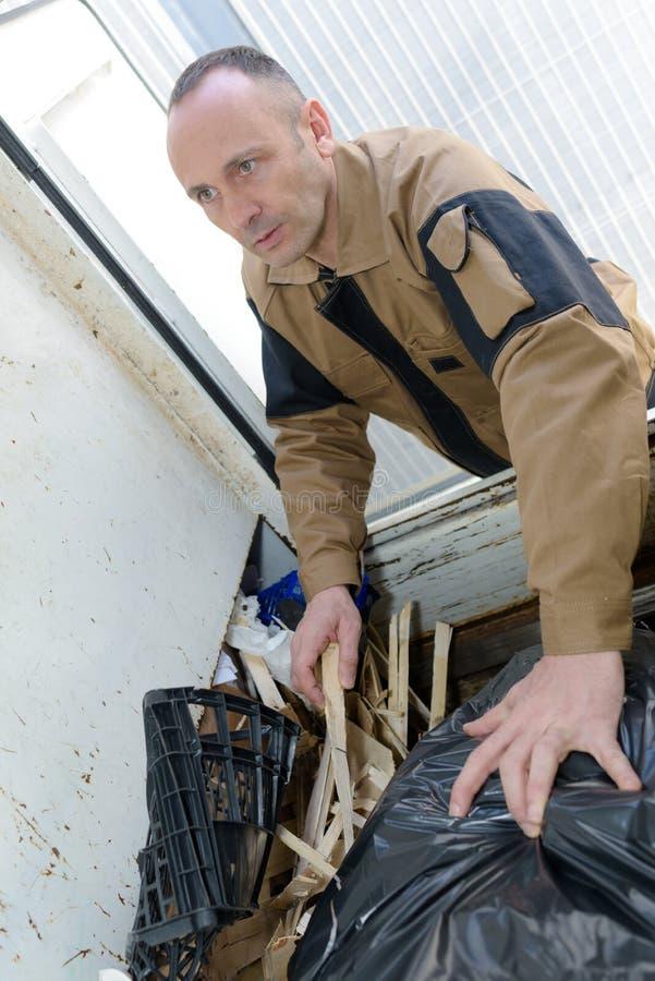 Bolso de basura del hombre que lleva en la descarga imagenes de archivo