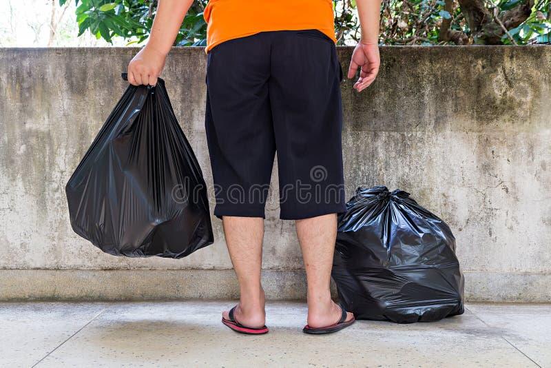 Bolso de basura del hombre que lleva joven fotografía de archivo libre de regalías