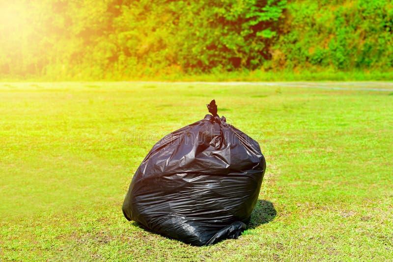 Bolso de basura en verde en naturaleza foto de archivo libre de regalías