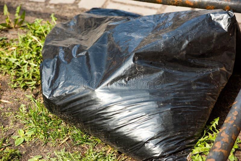 Bolso de basura plástico negro entre la hierba fotos de archivo libres de regalías