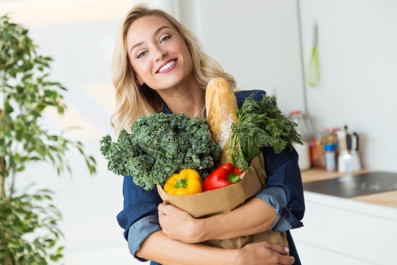 Bolso de compras hermoso de la mujer joven con las verduras en casa fotos de archivo