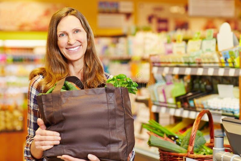 Bolso de compras sonriente de la explotación agrícola de la mujer imagenes de archivo