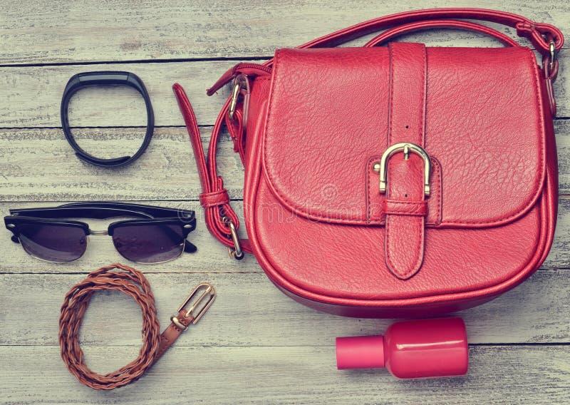 Bolso de cuero rojo y otros accesorios femeninos fotos de archivo libres de regalías