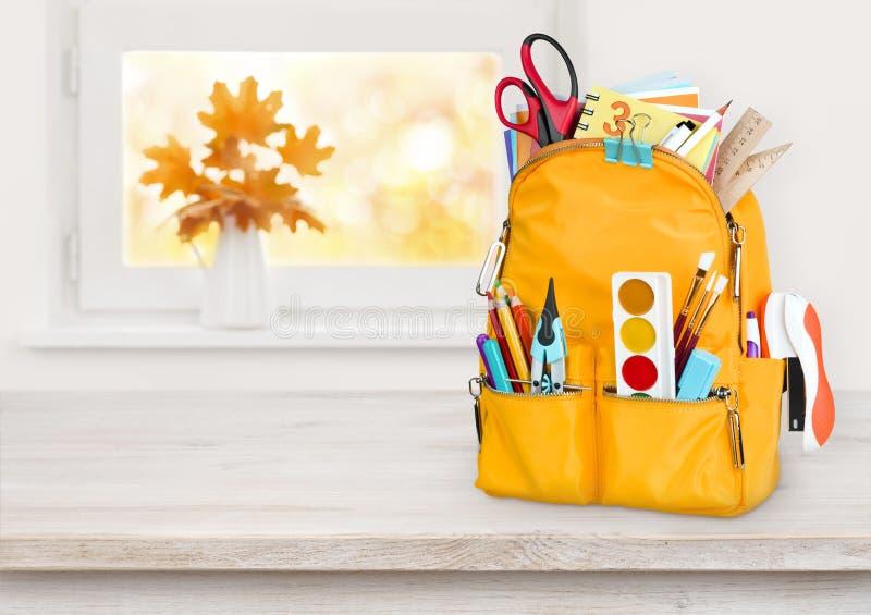 Bolso de escuela amarillo en la tabla de madera sobre fondo del alféizar del otoño imágenes de archivo libres de regalías