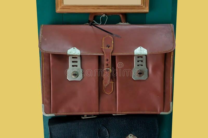 Bolso de escuela de cuero viejo que cuelga contra puerta de madera verde foto de archivo libre de regalías