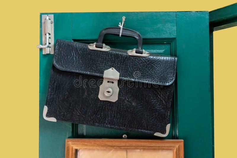 Bolso de escuela de cuero viejo que cuelga contra puerta de madera verde imagen de archivo