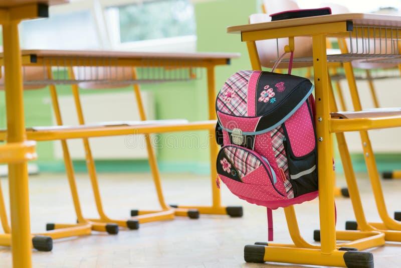 Bolso de escuela y caja de lápiz femeninos rosados en un escritorio en una sala de clase vacía Primer día de escuela imagen de archivo libre de regalías