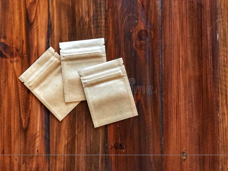 Bolso de la cerradura de la cremallera del papel de 3 Kraft en la tabla de madera del vintage foto de archivo