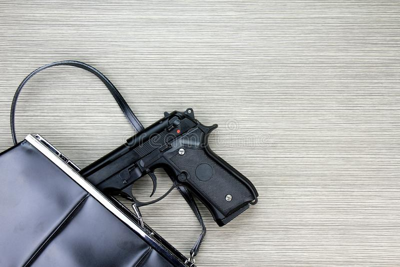 Bolso de la mujer con el arma ocultado, arma de mano que cae de un monedero del ` s de la mujer imagen de archivo