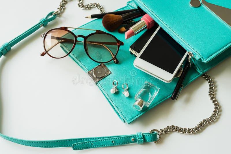 Bolso de la mujer con maquillaje, el teléfono móvil y los accesorios fotografía de archivo