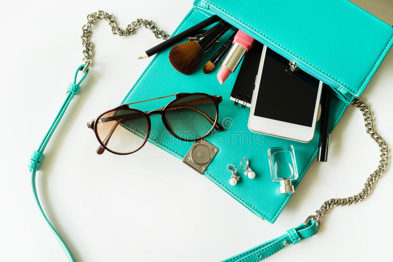 Bolso de la mujer con maquillaje, el teléfono móvil y los accesorios foto de archivo