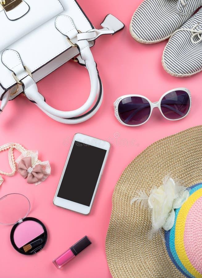 Bolso de la mujer con maquillaje y accesorios aislados en backg rosado imagen de archivo