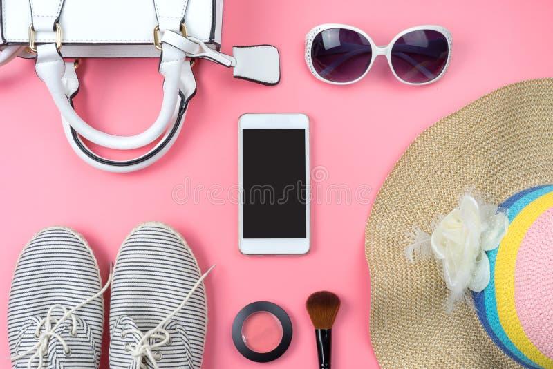 Bolso de la mujer con maquillaje y accesorios aislados en backg rosado fotos de archivo