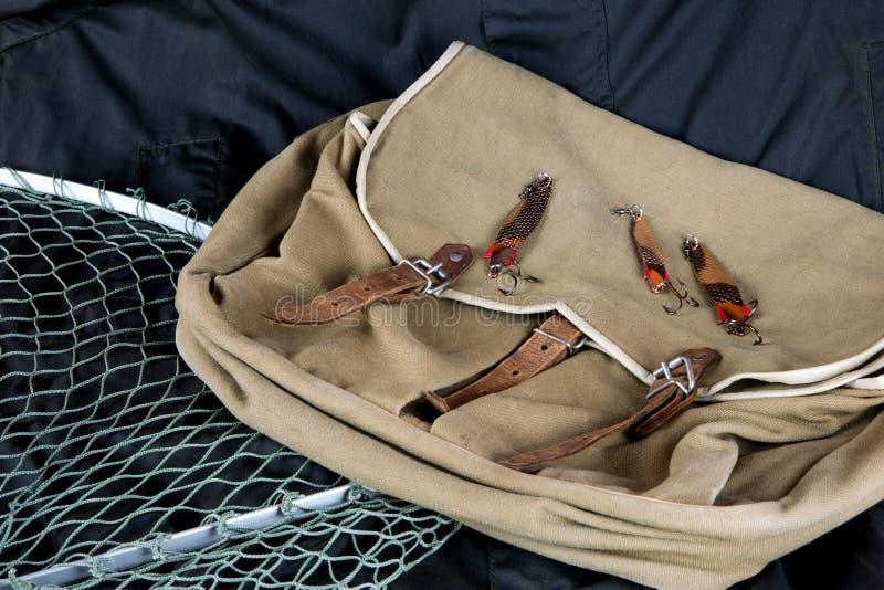 Bolso de la pesca y red de aterrizaje con señuelos en la capa al aire libre imagen de archivo libre de regalías