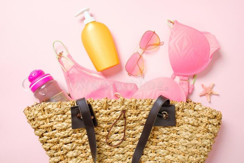 Bolso de la playa con ropa y accesorios de moda del verano en fondo rosado Materia femenina del encanto de la visi?n superior, tr foto de archivo