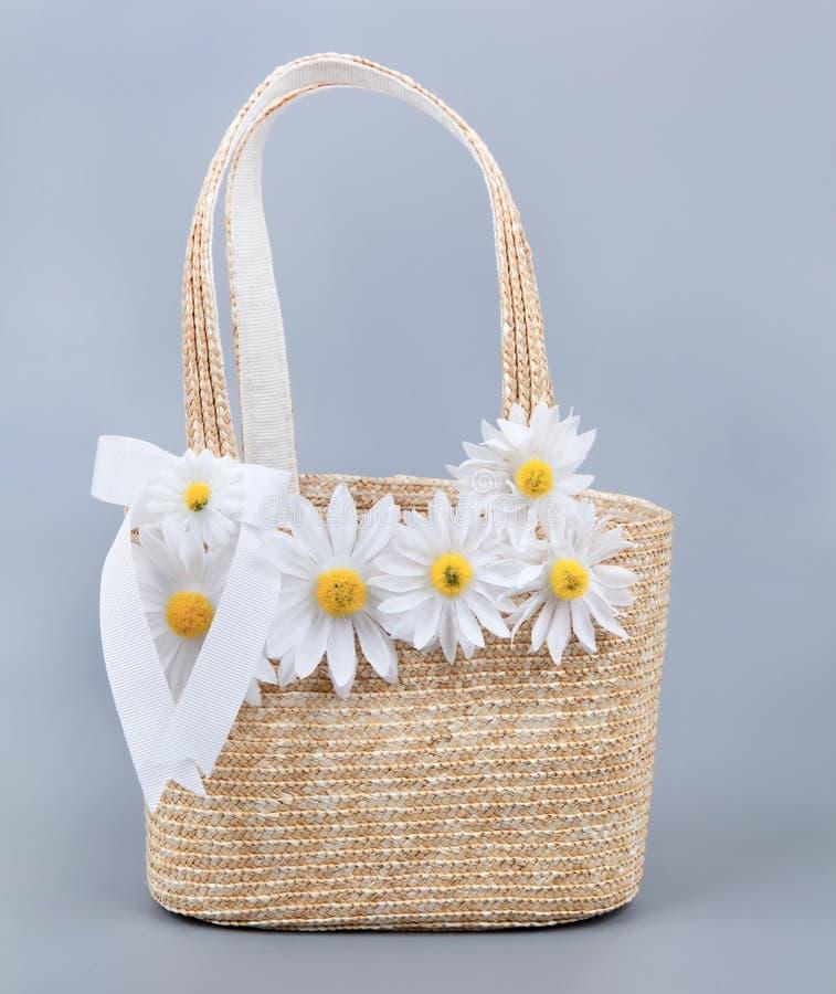 Bolso de la playa de la paja con las flores imagen de archivo