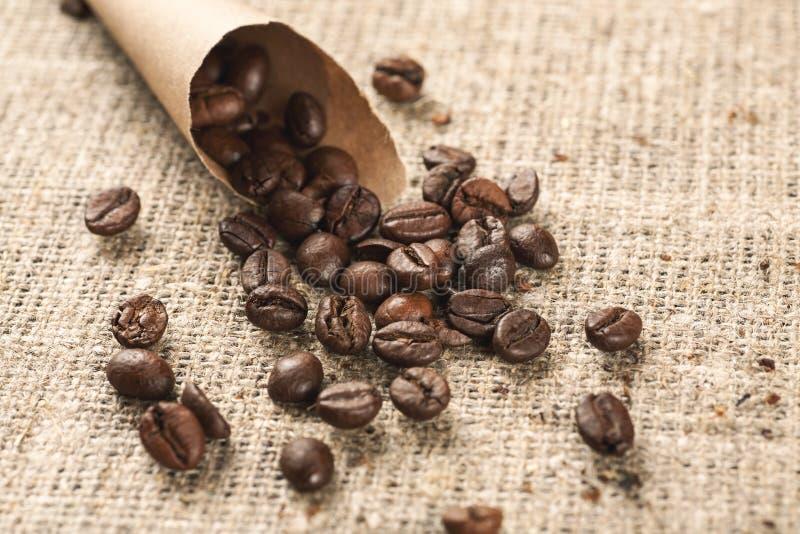 Bolso de papel del cono con los granos de café asados en una arpillera foto de archivo