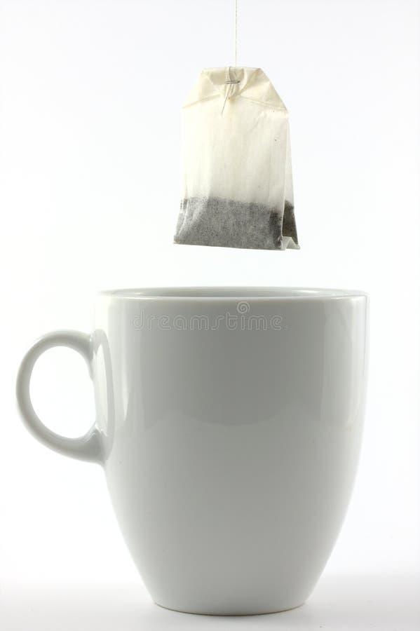 Bolso de té y una taza blanca imágenes de archivo libres de regalías