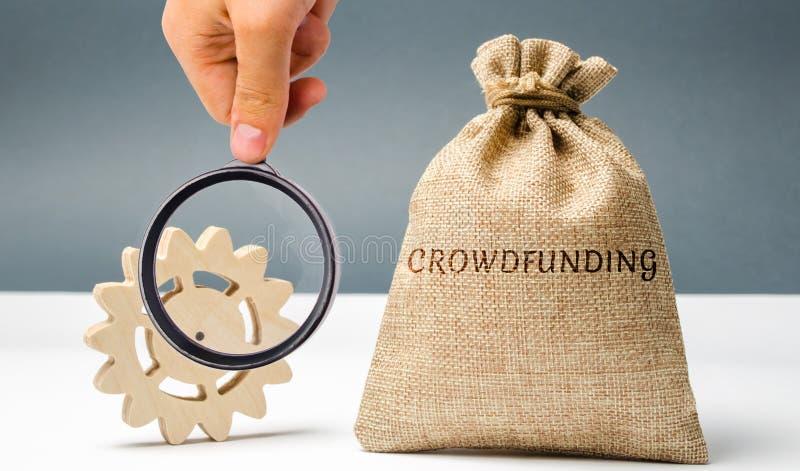 Bolso del dinero con crowdfunding y el engranaje de la palabra El concepto de aumentar los fondos para una compañía crowdfunding  imagen de archivo