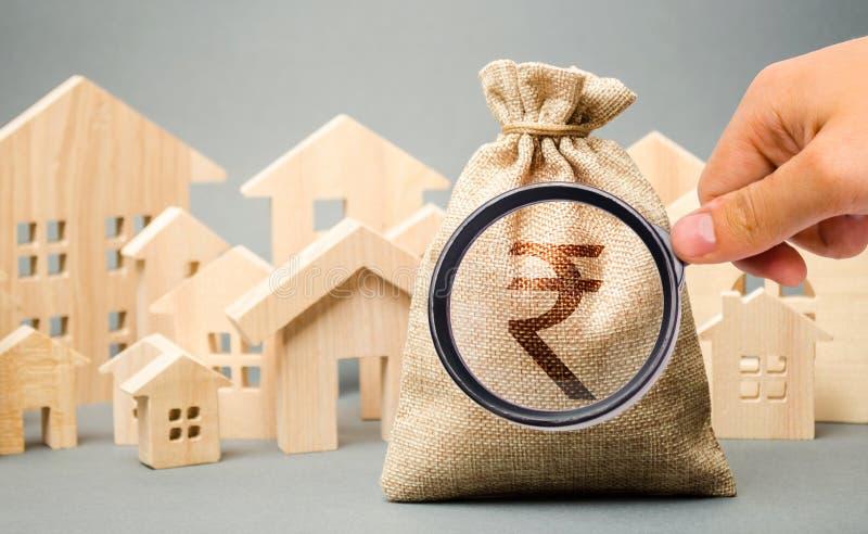 Bolso del dinero con un rupia de la rupia india de la muestra y casas de madera El concepto de mercado inmobiliario Tasación y de foto de archivo libre de regalías