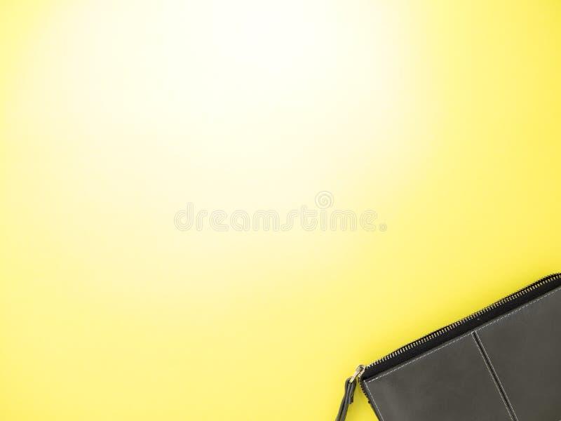 Bolso del maquillaje en el fondo amarillo de papel foto de archivo