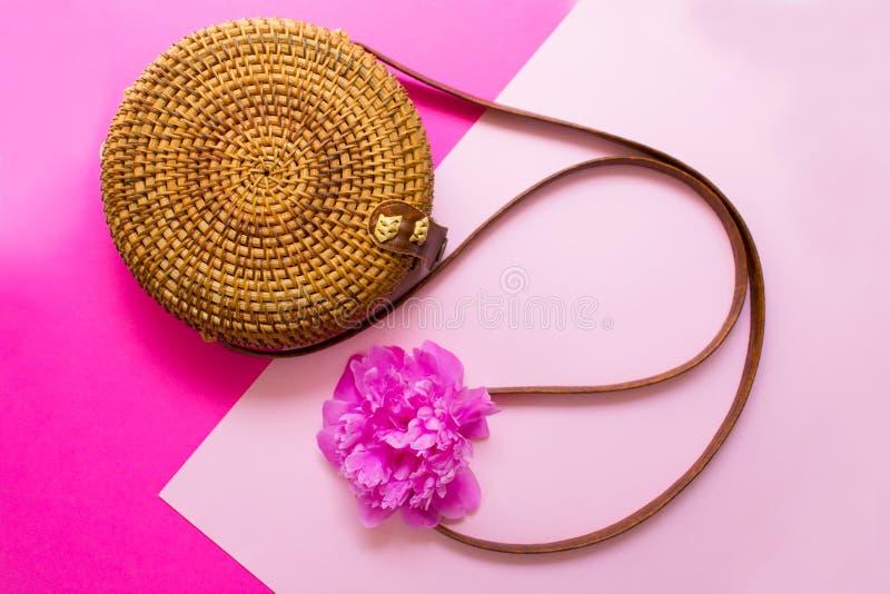 Bolso del verano de las mujeres de la paja y flor elegantes de la peon?a en un fondo rosado Concepto de las vacaciones de verano imagenes de archivo