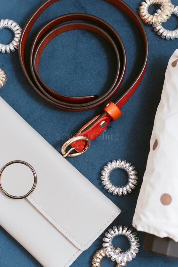 Bolso elegante, cartera, correa, scrunchy en un fondo azul Concepto elegante, endecha plana fotografía de archivo