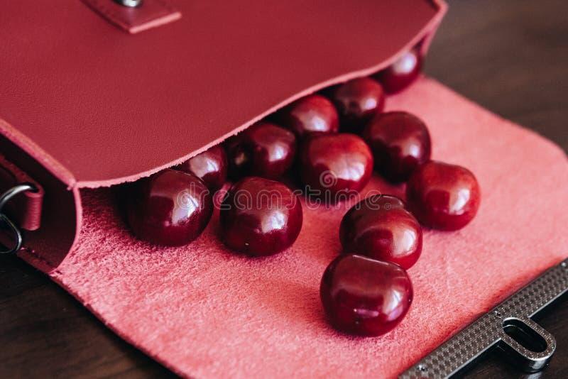 Bolso elegante con los cosméticos y las cerezas maduras foto de archivo